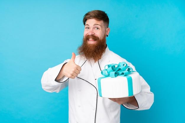 Pasticcere rossa con la barba lunga in possesso di una grande torta sul muro blu isolato con il pollice in alto perché è successo qualcosa di buono
