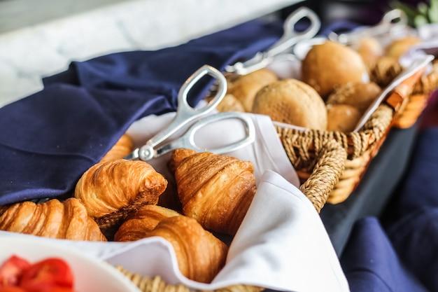 Pasticceria nella vista laterale dei panini del croissant del cestino di vimini