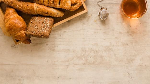 Pasticceria piana di disposizione in scatola di legno e tè con lo spazio della copia