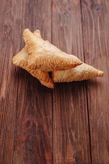 Pasticceria triangolare fresca su un tavolo di legno