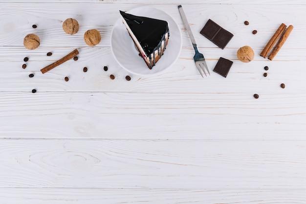 Pasticcino; noci; cannella; chicchi di caffè; forchetta e barretta di cioccolato su sfondo bianco in legno