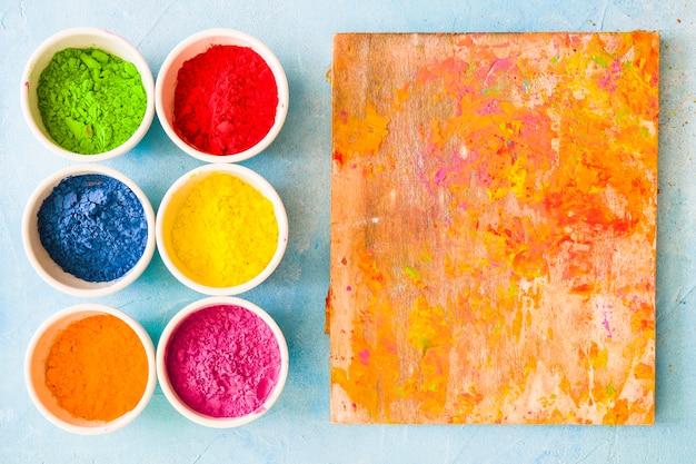 Pasticcio della tavola di legno con polvere di colore di holi su fondo dipinto