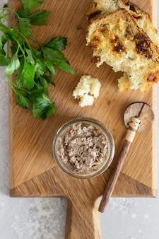 Pasticcio di fegato in un barattolo di vetro con pane fresco e prezzemolo su un tagliere di legno.