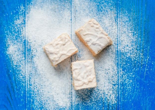 Pastila pezzi sullo sfondo blu in legno coperto di zucchero a velo, vista dall'alto