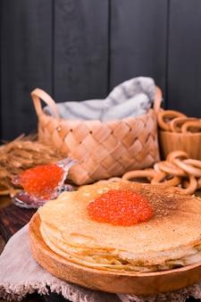 Pasto del festival della settimana di shrovetide maslenitsa. pila di pancake russi con caviale rosso. stile rustico, spazio libero per il testo,
