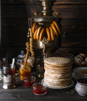 Pasto del festival shrovetide maslenitsa butter week. pila di pancake russi, samovar