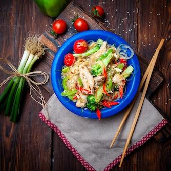 Pasto delizioso di vista superiore in piatto blu con le cipolle verdi, i pomodori e le bacchette su fondo di legno scuro.