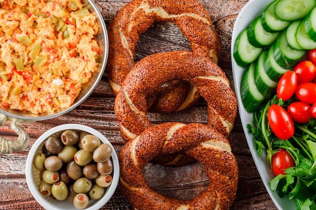 Pasto delizioso di vista superiore in piatto con bagel turco, insalata, sottaceti in ciotola su superficie di legno
