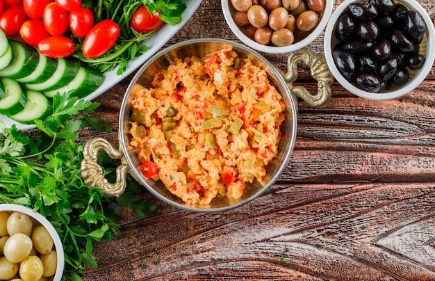 Pasto delizioso di vista superiore in vaso con insalata, sottaceti in ciotole su superficie di legno