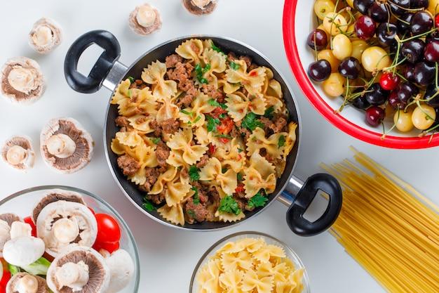 Pasto di pasta in padella con pasta cruda, funghi, pepe, pomodoro, ciliegie