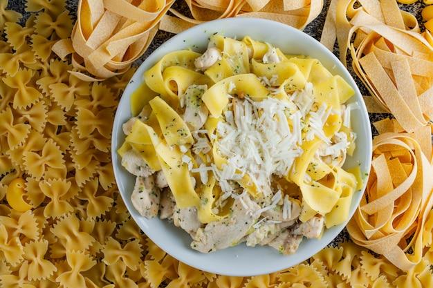 Pasto di pasta in un piatto su una pasta cruda