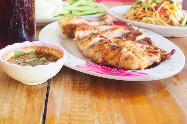 Pasto piccante in stile tailandese, pollo alla griglia con insalata di papaya piccante e bibita fresca