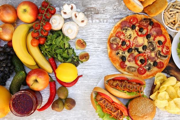 Pasto rapido ed alimento sano sulla vecchia tavola di legno bianca. concetto che sceglie nutrizione corretta o di cibo spazzatura. vista dall'alto.