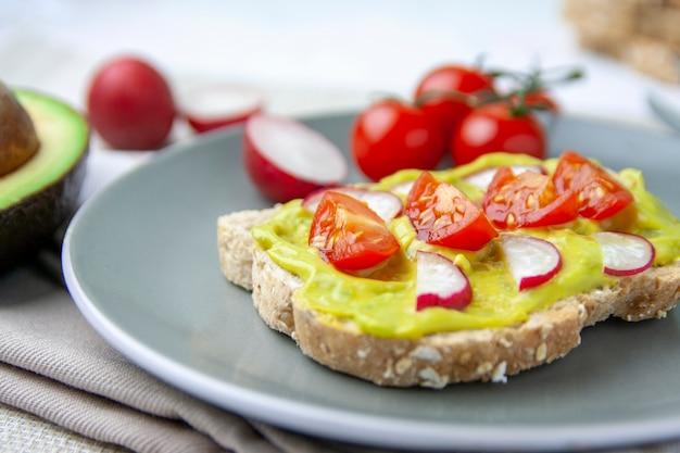Pasto sano con pane tostato con avocado, pomodoro e ravanello su un piatto e gli ingredienti