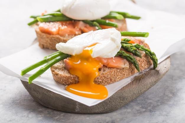 Pasto vegetariano sano. toast, uovo in camicia, asparagi, pesce salmone. tavolo di pietra dieta pulita. cibo organico.