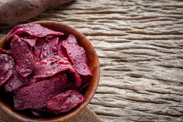 Patata dolce viola nella tazza, disposta su un pavimento di legno marrone.