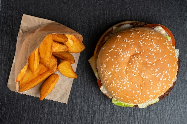 Patata in carta accanto a un hamburger su un'ardesia, piatti di pietra nera. vista dall'alto.