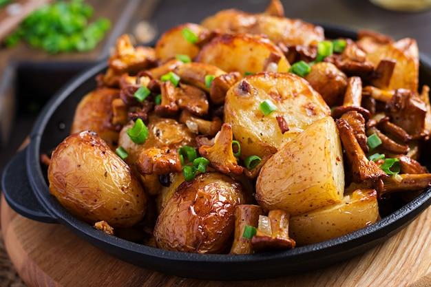 Patate al forno con aglio, erbe e finferli fritti in una padella di ghisa.