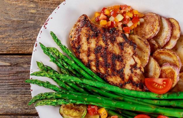 Patate al forno e asparagi su un piatto bianco con pomodoro