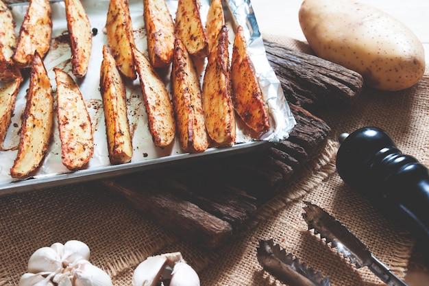 Patate al forno sul vassoio con peperoni neri e aglio sul bordo di legno rustico. cibo vegano o spuntino cibo salutare