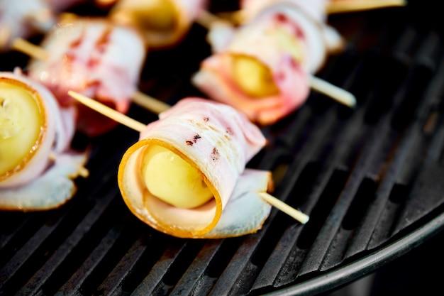 Patate alla griglia con pancetta sulla griglia a gas.