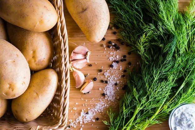 Patate, aneto, aglio, sale e pepe su un legno. vista dall'alto