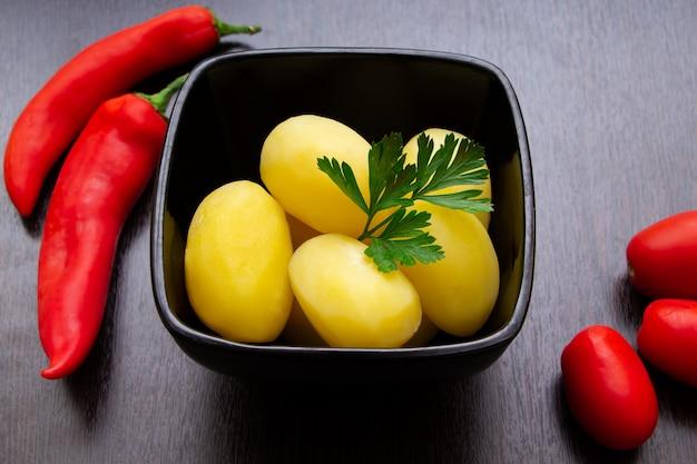 Patate bollite con peperoncini e pomodori su uno sfondo scuro