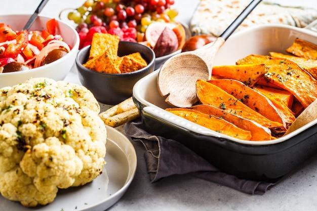 Patate dolci al forno, cavolfiore, frutta, insalata di verdure e tortilla con verdure su uno sfondo bianco.