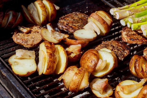 Patate e carne arrostita sulla griglia del barbecue degli spiedi