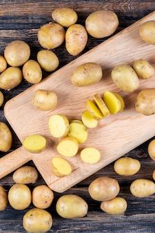 Patate e patate affettate su un tagliere su una tavola di legno
