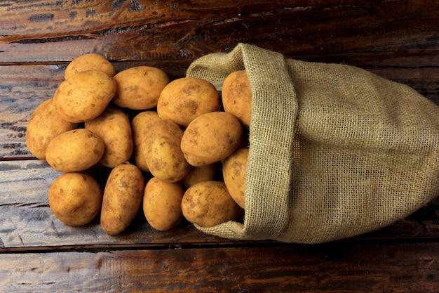 Patate fresche e crude raccolte dalla piantagione e collocate in una borsa rustica sul tavolo di legno