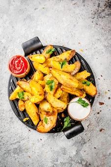 Patate fritte al forno con erbe rosse aglio e salse bianche su sfondo grigio pietra