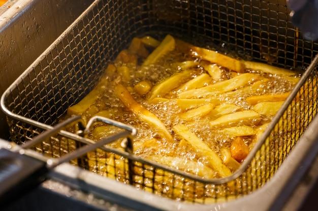 Patate fritte che cuociono fritte in olio bollente nel cestino della macchina per friggere