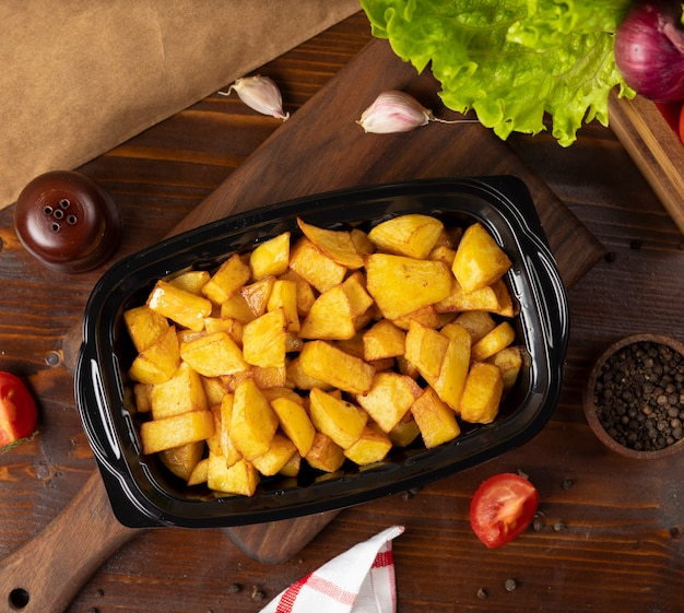Patate fritte con erbe da asporto in contenitore nero.