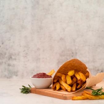 Patate fritte con ketchup e copia spazio