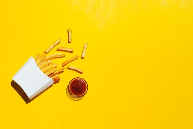 Patate fritte con ketchup su fondo giallo