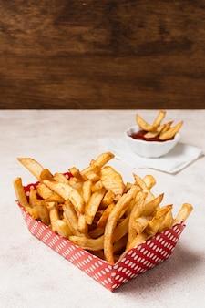 Patate fritte con ketchup sulla tavola bianca