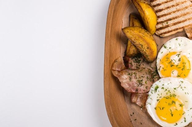 Patate fritte con pancetta affumicata, uova e pane per la colazione, primi piani su fondo di legno. vista dall'alto con spazio di copia