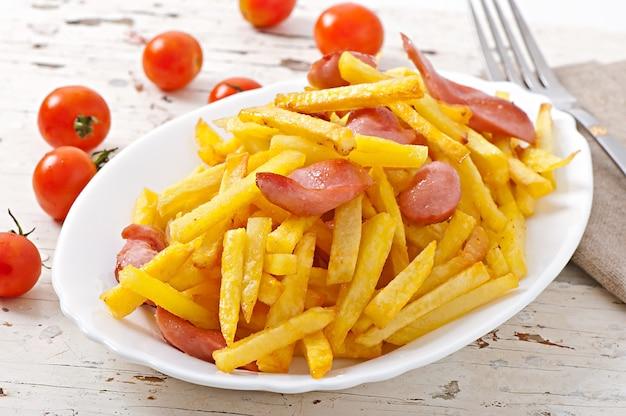 Patate fritte con salsiccia su un piatto