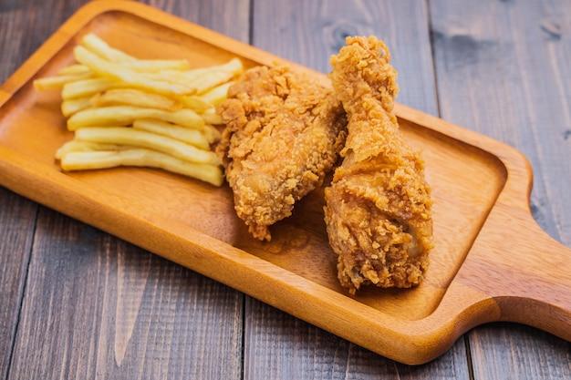 Patate fritte croccanti del pollo fritto e delle patate fritte sul piatto di legno