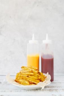 Patate fritte di vista frontale sulla tavola di legno
