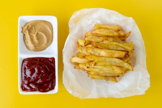 Patate fritte di vista superiore con fondo giallo