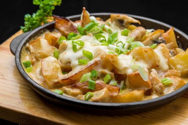 Patate fritte dorate deliziose in caffè degli alimenti a rapida preparazione. cibo spazzatura malsano ma gustoso. bastoncini di patate fritte con pancetta e formaggio