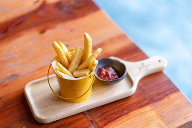 Patate fritte e ketchup sul bordo di legno