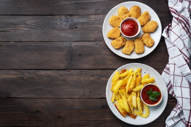 Patate fritte e pepite di pollo con salsa di salsa ketchup. concetto di fast food di cibo malsano. tavolo di legno. copia spazio.