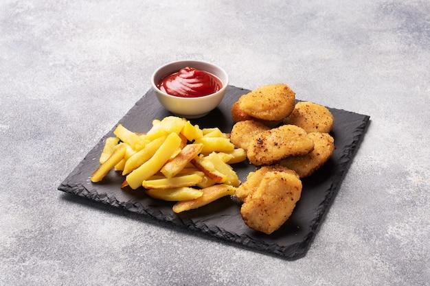 Patate fritte e pepite di pollo con salsa di salsa ketchup. concetto di fast food di cibo malsano. tavolo in cemento grigio copia spazio.