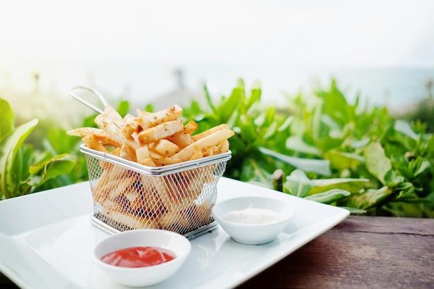 Patate fritte francesi su setaccio a maglie in metallo con salsa a due tuffi