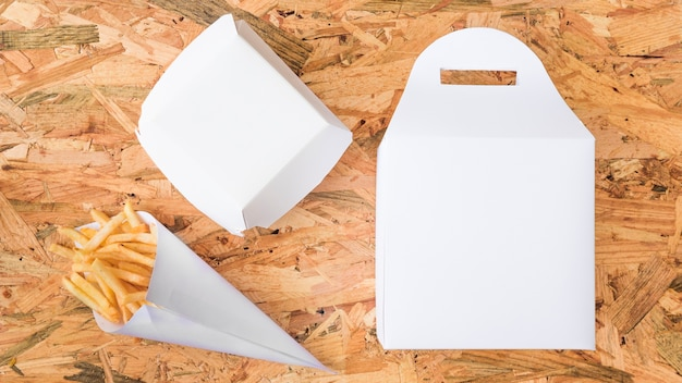 Patate fritte in cono di carta e pacchetto bianco su fondo di legno