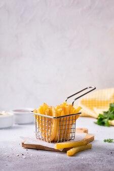 Patate fritte in un cestino su calcestruzzo