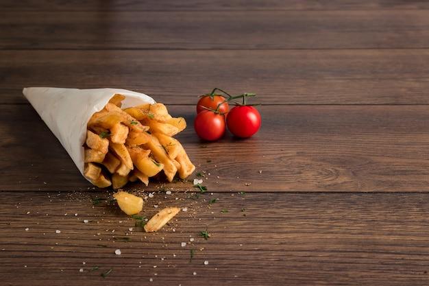 Patate fritte, in un sacchetto di carta su legno marrone